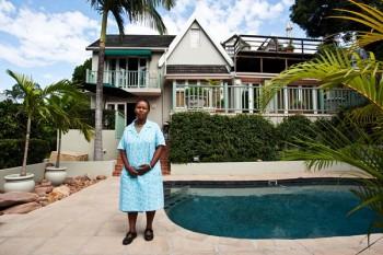 Ntombi Mkize i arbeidsklede ved bassenget til arbeidsgivarane sine. Eigarane brukar berre huset og bassenget som feriebolig. Sjølv bur Ntombi og dottera Ntando i eit lite rom på baksida av huset.